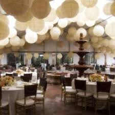 Various sized paper lanterns hang from the ceiling of the wedding reception.