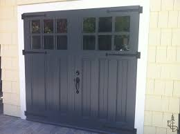 black carriage doors on yellow house with white trim via evergreen carriage doors