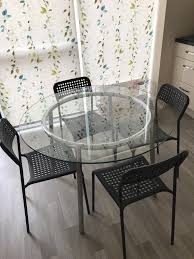 round glass table with 4 black chair from ikea