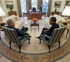 inside the oval office. george w bush sits in the left foreground while barack obama to right inside oval office h