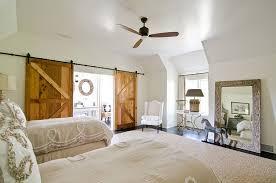 ... Sliding barn doors add texture to the cool bedroom [Photography:  Virtual Studio Innovatons]