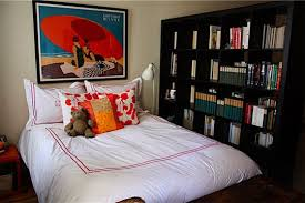 The other side of the room divider--an oh-so-cozy-bed and a large framed  print above keep our eyes focused on the design (and not the small size of  the ...
