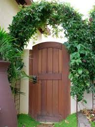 exterior wood gates. wooden fence gates with arched arbor and passiflora vines exterior wood o