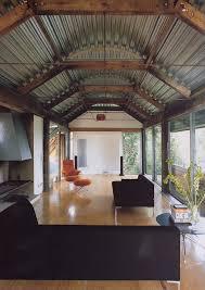 corrugated metal ceiling basement living room industrial with black sofa barn light floor length windows