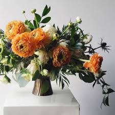 a stylish Thanksgiving arrangement with orange, white blooms, greenery and  thistles