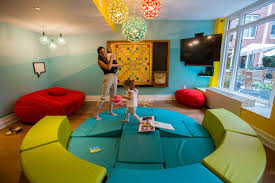 Talli Levine, 30, with her daughter Olivia, 1, and son, Harrison, in the  playroom at the Brompton on the Upper East Side. Credit Hiroko Masuike/The  New York ...