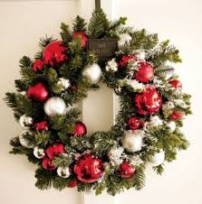 To decorate an evergreen wreath in a stylish way hang ornaments as if on a  tree