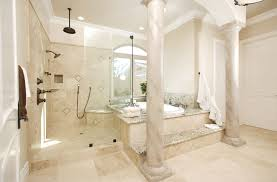 Ultra luxurious bathroom features beige tile throughout, with immense glass  enclosure shower standing next to