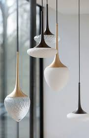 group of lights with natural shapes and patterns black and gold brass pendant lighting