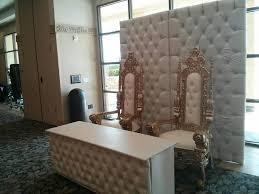 white leather tufeted wedding backdrop and matching table with gold throne chairs