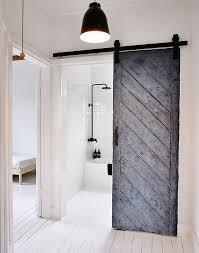 reused old barn door creates a fabulous entrance for the scandinavian bathroom design mr