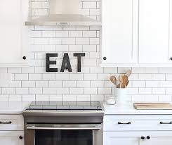 with oil rubbed bronze paint to mimic weathered metal letters white kitchen cabinets with cambria torquay quartz countertops and subway tile backsplash