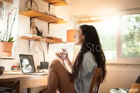 Sunny day home office Office Desk Woman In Blue Shirt Having Breakfast In Home Office And Looking Out Of The Window On Adobe Stock Woman In Blue Shirt Having Breakfast In Home Office And Looking Out
