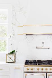 alyssa rosenheck white and gold french kitchen hood and stove with white quartz marble like countertops