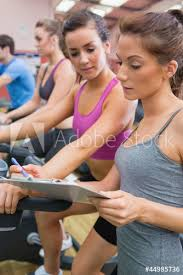 gym instructor gym instructor helping woman on exercise bicycle buy this stock