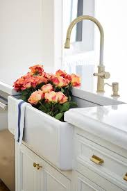 a white farmhouse kitchen sink features a brass gooseneck faucet in a white kitchen island with brass pulls on off white cabinets