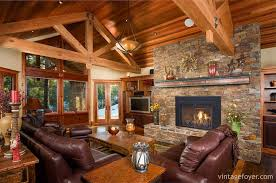 cozy living room with fireplace. The Contrasting Wood Ceiling And High Beams Gives This Living Room A Natural Cabin Look. Dark Stone Fireplace Adds To Comfort Mauve Cozy With