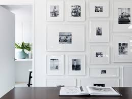 gallery wall of photos with wide white mats and white frames.