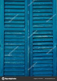 wooden window shutters in blue antique homemade shutters on the stock photo