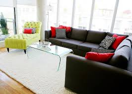 black sectional concrete column glass coffee table grey grey sectional lime green chaise printed pillows red pillows rug tall windows white walls