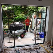 old window and brickwork below is carefully removed to make new aperture for french doors