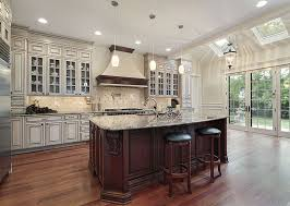 luxury kitchen with white cabinetry and large cherry wood dining island