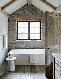 faux stone wall and weathered wood on the floor make this bathroom  cabin-like