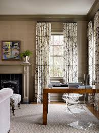 living room features walls clad in phillip jeffries rivets wallpaper on upper walls and taupe wainscoting on lower walls flanking a taupe fireplace mantle