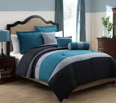 teal and gray comforter with sham and cushion also neckroll placed on cream queen