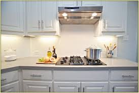 white glass subway tile backsplash with wooden kitchen cabinets also