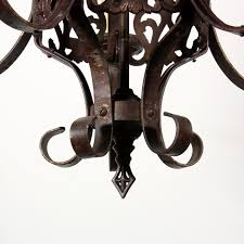 a fabulous antique iron five light chandelier with shields dating from the 1920 s still in its original finish this spanish revival chandelier begins