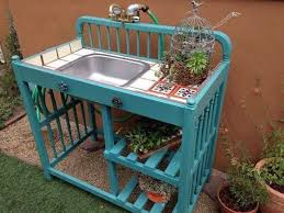 baby changing table repurposed into a gardening table with a sink