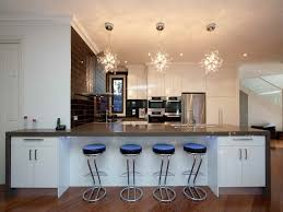 stunning kitchen with coffered ceiling adorned a pair of silver leafed crystal chandeliers over an expansive island sink lined by the chandelier in is