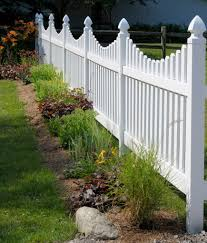 A lovely vinyl picket fence in white that meets a split rail fence. When  fences