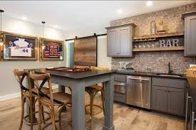 industrial kitchen with brick wall design and hardwood flooring along with white walls and wine glass
