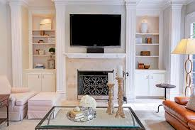 the family room features a gorgeous marble fireplace custom built ins stone floors surround sound system and a wall of french doors which view the