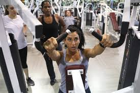 a gym trainer demonstrates how to use a pice of workout equipment at la fitness in