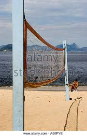 chair volleyball net. man sitting in a chair at the end of volleyball net on brazillian beach c