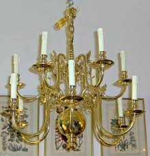 a handsome 18th c dutch style baroque manner 2 tier 12 light solid brass chandelier with turned baer supporting s scroll arms ending is a massive