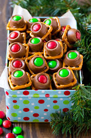 a gift tin full of colored rolo pretzels