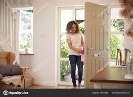 opening front door. Woman Opening Front Door \u2014 Stock Photo R