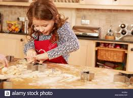 Girl Baking Star Shape Pastry At Kitchen Table Stock Photo