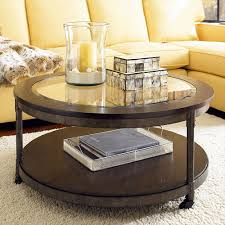 saving small living room spaces with round brown wood coffee table with glass top and metal frame on wheels plus white rugs and light yellow leather sofa