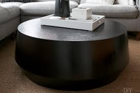 the black round coffee table from crate and barrel is the perfect choice for this living
