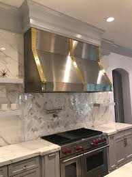 custom vent hoods. Handcrafted Custom Brushed Finish Stainless Steel Vent Hood With Brass Trim Bands #venthoods #luxurykitchens #customkitchens #interiordesign #elegantdesign Hoods