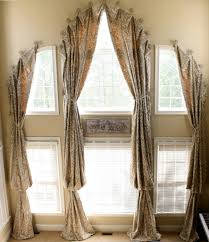 Medallion hung draperies over arched windows with tie backs, adding wood  blinds for privacy.