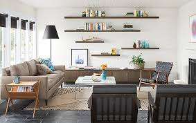 in this cozy living room the wall of float shelves shares the same finish as the keaton cabinets beneath the ira wood chair coordinates with the fitz end