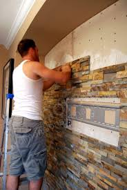 flat screen tv installed on stacked stone wall installing stone