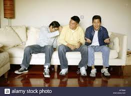 3 men watching tv on sofa stock photo royalty image 3 men watching tv on sofa