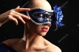 portrait of beautiful woman with fancy glitter makeup and masquerade mask on dark background stock